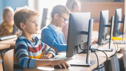 Elementary School Science Classroom: Smart Little Schoolchildren Sitting in Row and Work on...