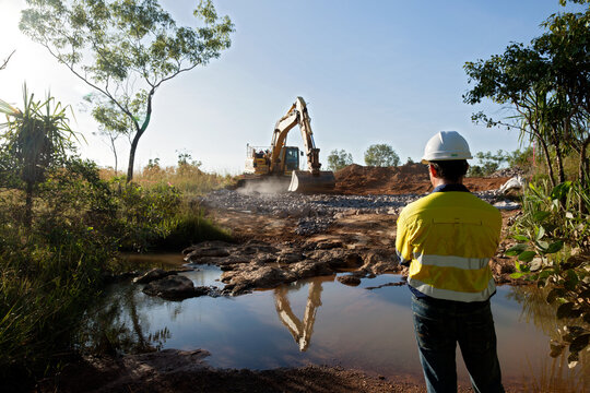 Industrial worker overseeing a large digger moving rocks on an industrial building site