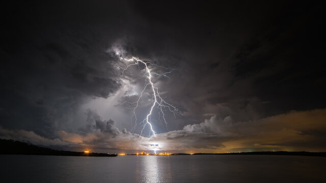 View of lightning over factory with ocean in foreground at night