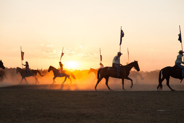 Shadows and silhouettes of horses and riders with australian flags on dust at sunset
