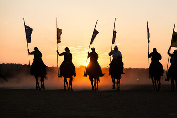 Line of silhouetted horses and riders with flag poles charging at sunset