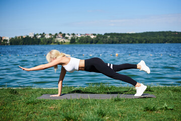 Young blond woman, wearing black leggings and white top, doing plank, lifting her arm and leg, on grey yoga mat by lake in summer. Female sport training outside on fresh air. Healthy lifestyle.