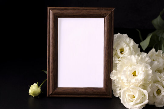mockup of empty mourning frame next to white flowers. death and sorrow concept