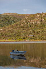 Boat on an anchor in the scenic delta of river in Ifjord in Finnmark, Norway