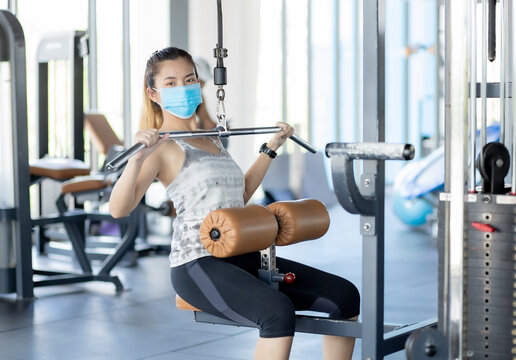 Women wearing masks exercise in the gym to keep social distance.