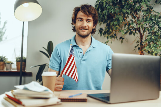 Young bearded businessman sitting at table with laptop and american flag