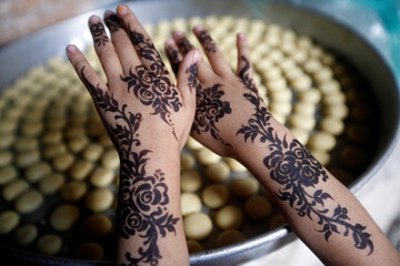 A girl displays a henna pattern applied on her hands for the Eid al-Adha festival at the old quarter of Sanaa