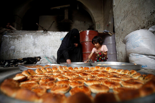 Woman and a girl prepare cookies for the Eid al-Adha festival at the old quarter of Sanaa, Yemen