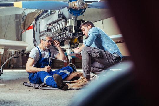 Aircraft mechanics in the hangar. Coworkers repairing an aircraft