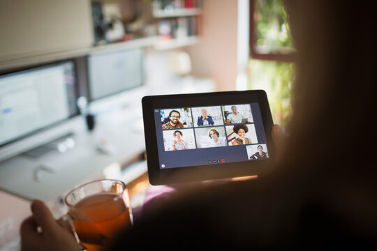 Woman video conferencing with colleagues on digital tablet screen