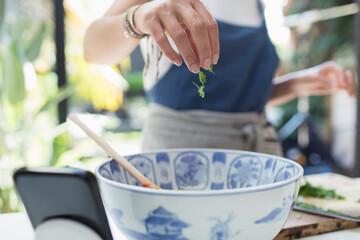 Woman sprinkling fresh herbs in bowl