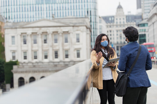 Business people in face masks talking on city bridge, London, UK