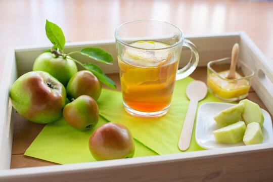 frisch aufgebrühter Apfeltee mit Apfelschale- und stücken auf einem Tablett