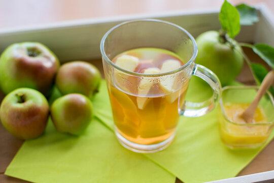 Apfeltee mit frischen Apfelstückchen und Honig auf einem Tablett