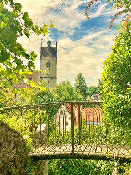 In the foreground a small romantic bridge and the parish church of Bregenz in the background.
