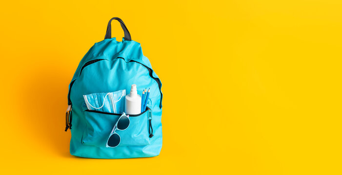 Back to school in pandemic. School backpack with face masks and disinfectant.