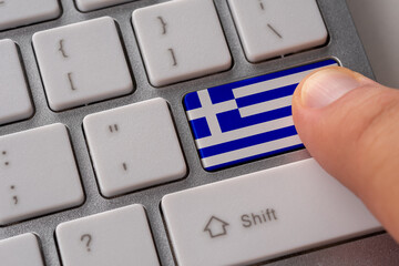 Male hand pressing keyboard button with flag of Greece on it. Online international business concept.