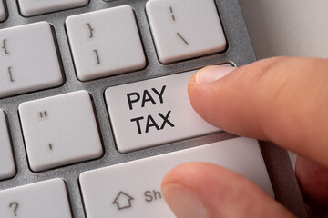 Male hand pressing keyboard button PAY TAX. Business online concept.