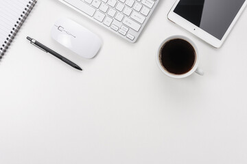 Workspace with computer keyboard, office supplies, and coffee cup on white background. Top view with copy space.