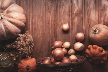 autumn pumpkins and other fruits and vegetables on a wooden table, top view