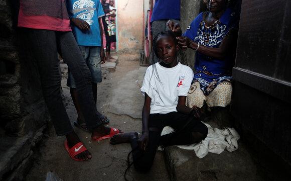 A girl has her hair braided ahead of the Muslim festival of sacrifice Eid al-Adha, in Dakar