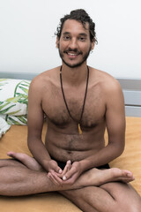 A young Afro European male Yogi does meditation and Hatha Yoga workout at home during lockdown.