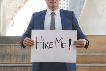 Asian businessman trying to find job and showing paper sign to tell other people that he looking for a job.