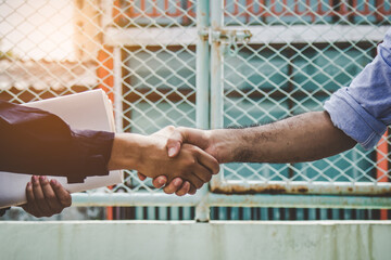 Successful deal, architect shaking hands with client in construction site after confirm blueprint for renovate building.