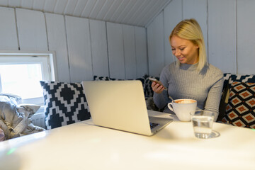 Happy young beautiful blonde woman using phone at home