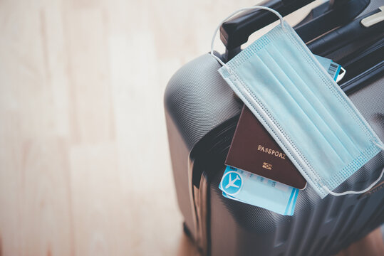 Passport and mask On luggage, concept tourism planning and new normal travel