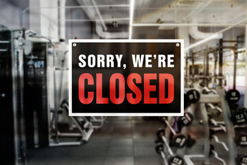 Image of a blurred gym background with closed sign in front. Closure or bankruptcy of gym or fitness center.