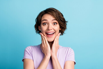 Portrait of astonished positive cheerful girl impressed wonderful bargain novelty touch face hands...