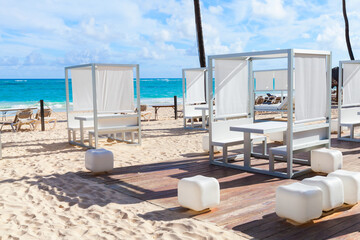 Gazebos are on sandy beach at sunny day