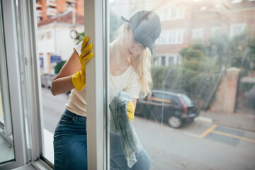 Woman cleaning window from the outside