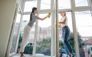 Two girls cleaning windows. Housecleaning, housework concept