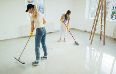 Two women cleaning floor with brush