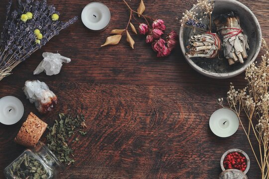 Dark brown wooden table background for text, decorated with witchy wiccan items to look esoteric and occult. Free writing space in the middle. Dried herbs, crystals, sage smudge sticks candles flowers