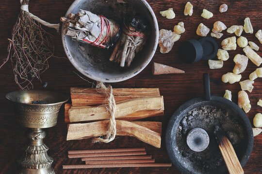 Flat lay various kinds of air element objects to use in witchcraft and wicca on witch's altar filled with sage smudge sticks, incense, Palo Santo tree, frankincense, charcoal disks for smoke cleansing