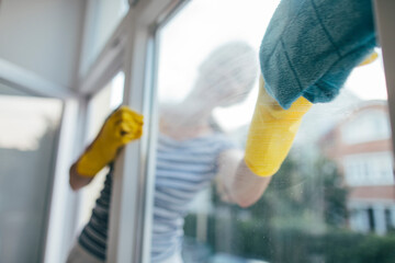 Selective focus of woman in gloves cleaning window with rag