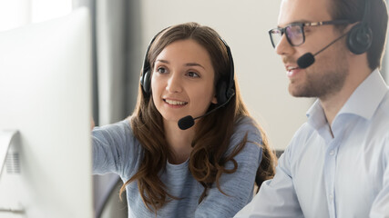 Smiling female mentor in wireless headset teaching call center operator intern close up, coach training customer support service staff, using computer, consulting client on phone, horizontal photo