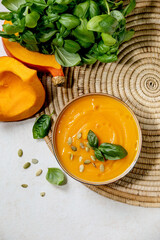 Bowl of pumpkin or carrot vegetarian cream soup decorated by fresh basil, olive oil and pumpkin seeds on white texture background with ingredients above. Flat lay, copy space