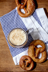 Glass of lager beer with traditional salted pretzels on white and blue napkin over wooden background. Flat lay, space. Oktoberfest theme