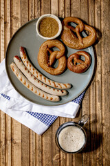 Bavarian traditional grilled pork sausages on ceramic plate served with german sweet mustard, mug of dark beer and pretzels bread on white and blue napkin over wooden background. Flat lay, space.