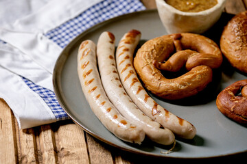 Bavarian traditional grilled pork sausages on ceramic plate served with german sweet mustard and pretzels bread on white and blue napkin over wooden background.