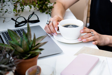 Woman's hand holding cup of coffee in cozy summer office with laptop and green plants