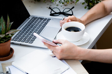 Woman's hand holding cup of coffee and smartphone in cozy office with laptop and green plants