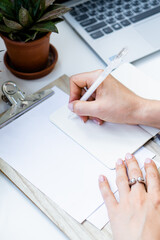 Woman's hands making notes in notepad in cozy summer office with laptop and green home plants