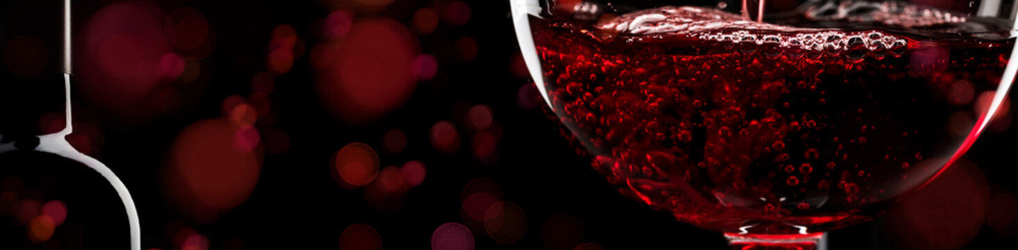 Red wine on black background, abstract splashing. Panoramic banner with copy space