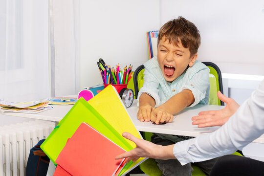 Boy with autism spectrum disorder throw textbooks and books from table in negative expression behavior sitting near teacher