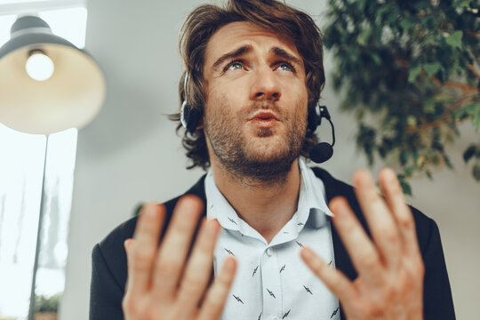 Close up portrait of an angry businessman with headset having stressful online conversation